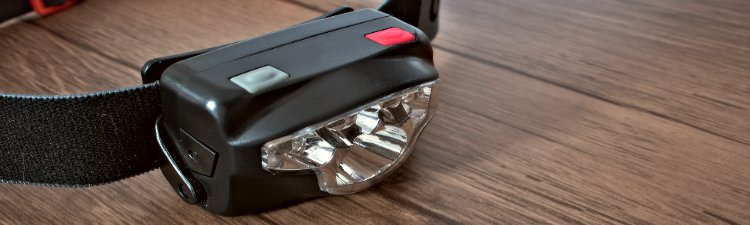 Black led headlamp turned off on a wooden table showing the elastic strap